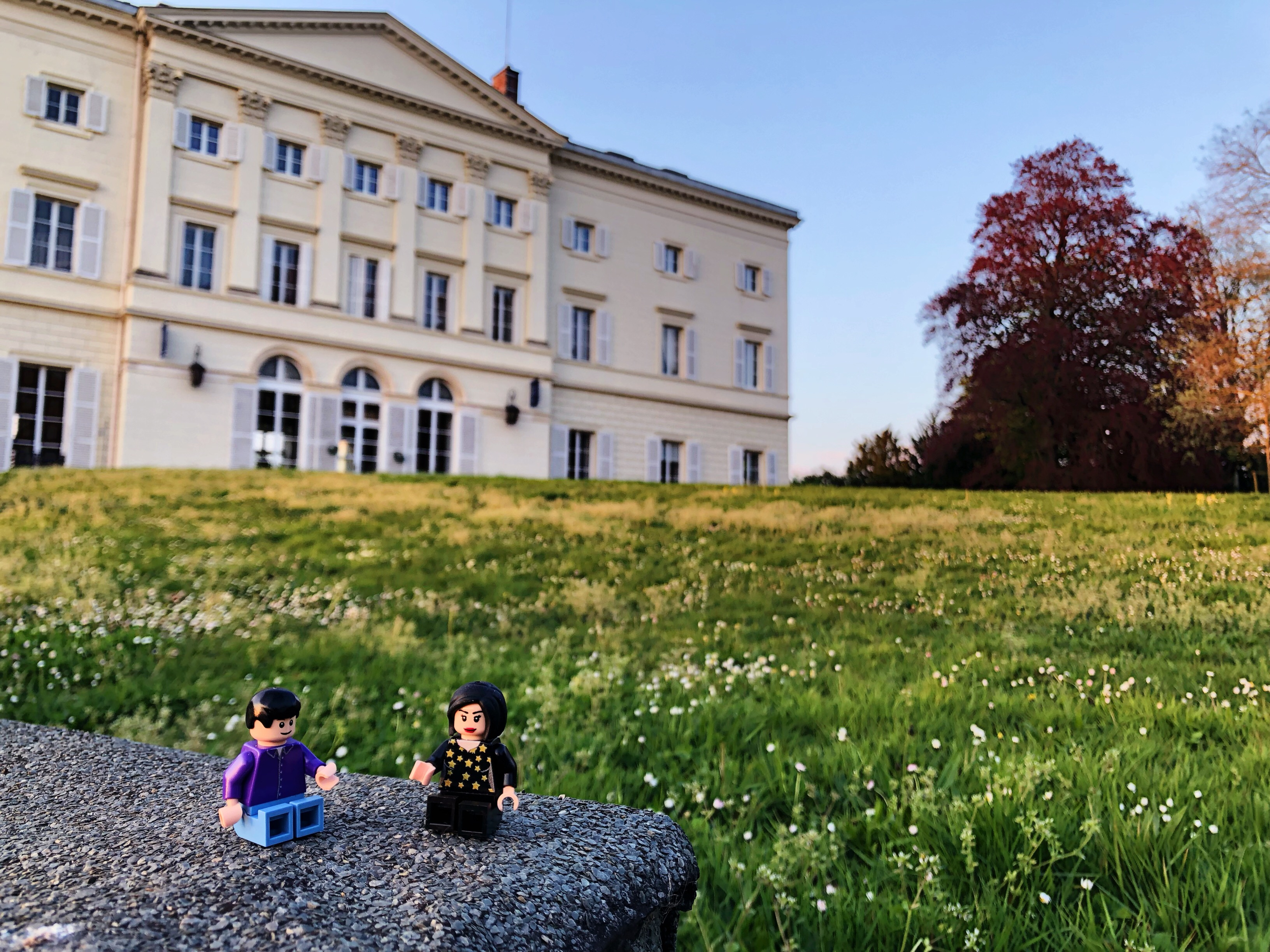 A lego man and woman sat together on stone in the grass in front of the HEC Chateau, which features in the background along trees of varying colours